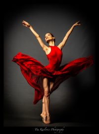 beautiful ballerina posing in a red dress in an emotive dance pose